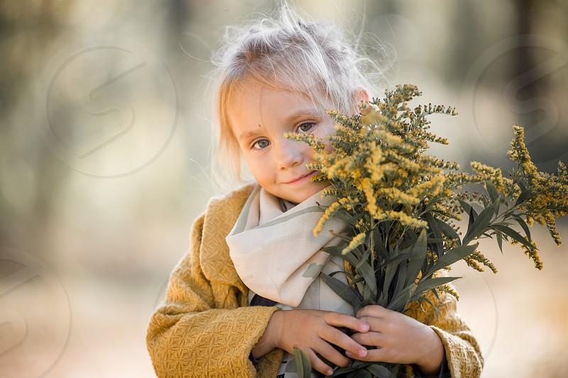Little girl in yellow coat at autumn park photo