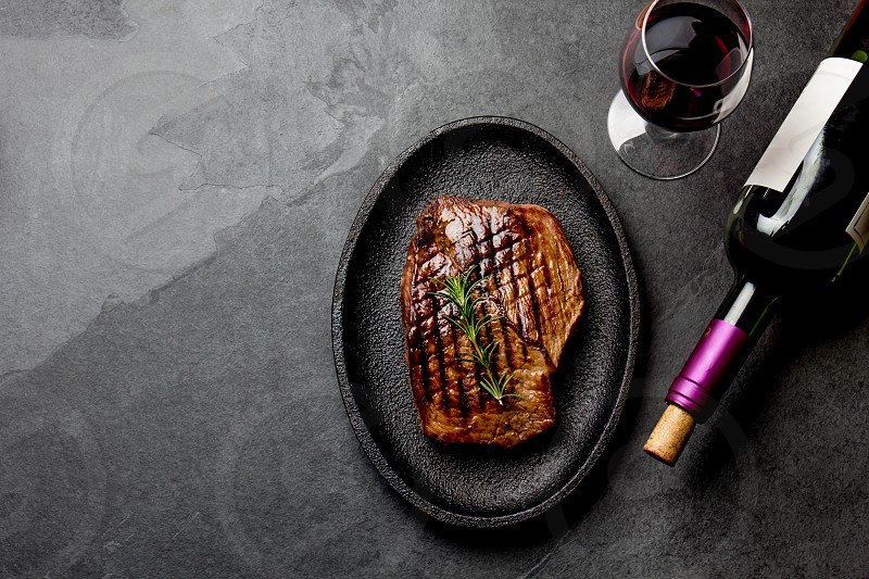 Grilled beef steak on black cast iron plate with red wine. Background with copy space. Barbecue bbq meat beef tenderloin. Top view slate background. photo