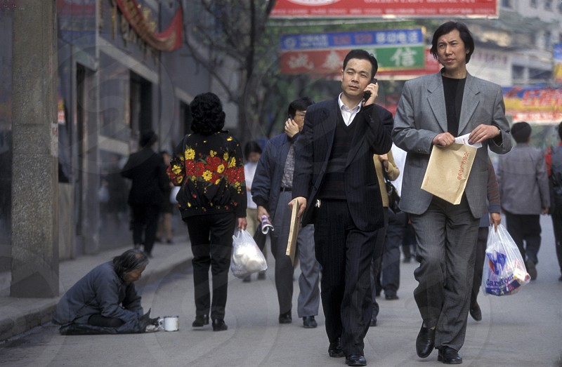 poor and Buisness People at the main square in the city of Chongqing in the province of Sichuan in china in east asia.  photo
