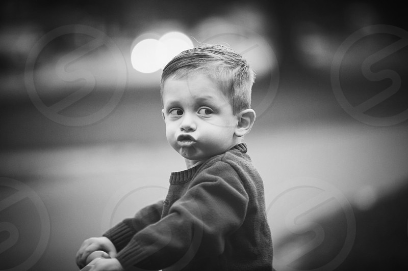 grayscale photography of toddler wearing sweater photo