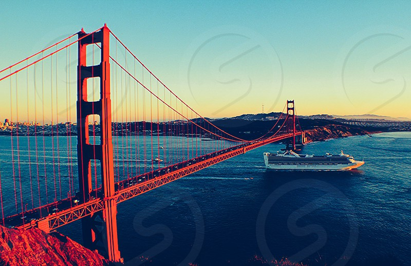 white and gray cruise ship under golden gate bridge photo