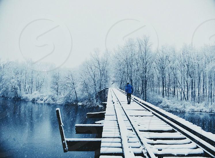 man in blue jacket walking on the bridge photo