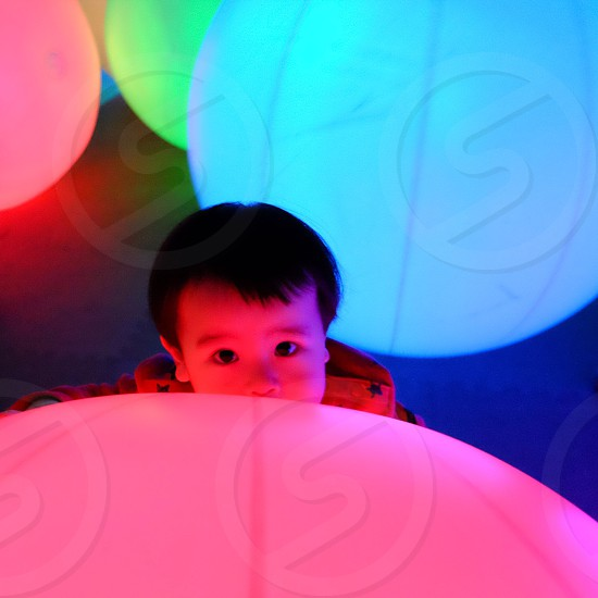 toddler standing between LED balls photo