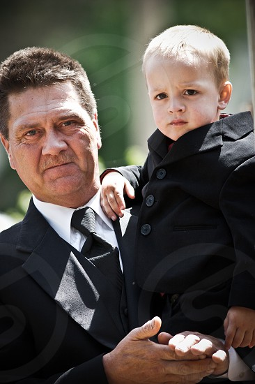 man carries a child both wearing 2-piece suits photo