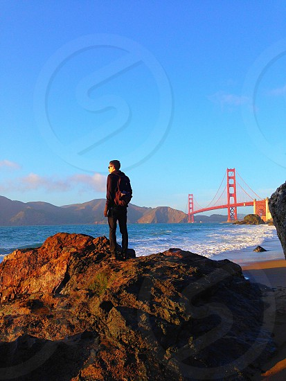 man in black jacket standing on rock photo
