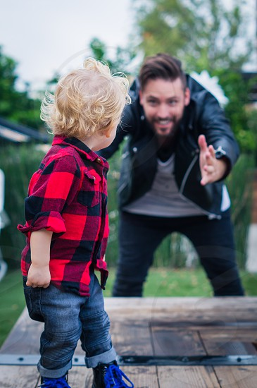 man in black leather jacket standing and looking at boy in red and black checked shirt photo