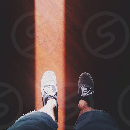 person black sneakers standing on brown wooden floor photo