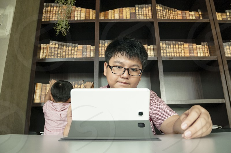 Kid using tablet computer in study room photo