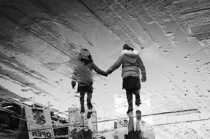 reflection of boy and girl on water holding hands photo