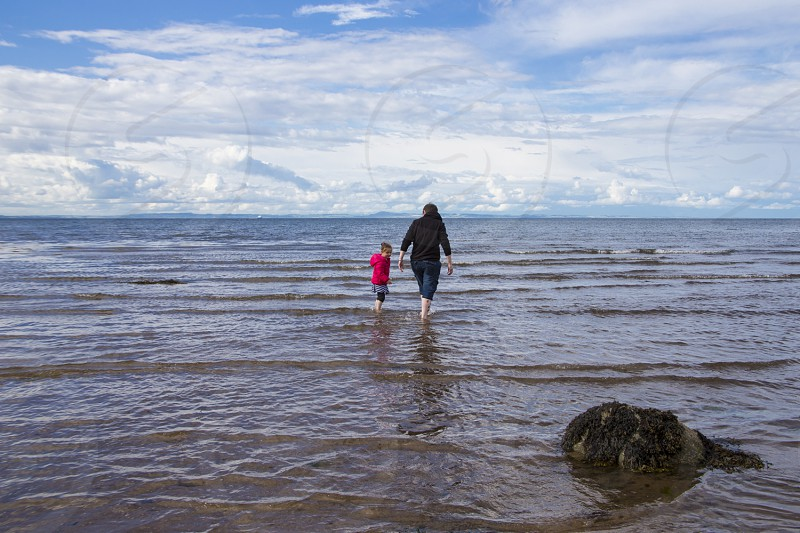 Young woman and little girl walking in the surf.  Seaside photo