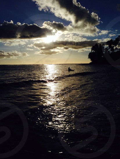 sun shining through clouds and over ocean waves photo