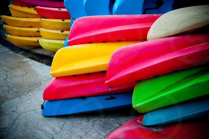 a large stack multi colored kayaks stacked up by beach photo