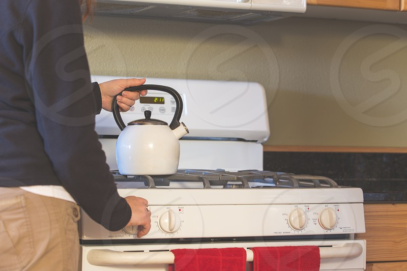A woman putting a teapot or kettle on a stove photo