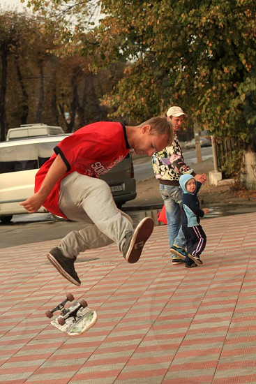 man in red crew neck shirt doing kick flip on his skateboard photo