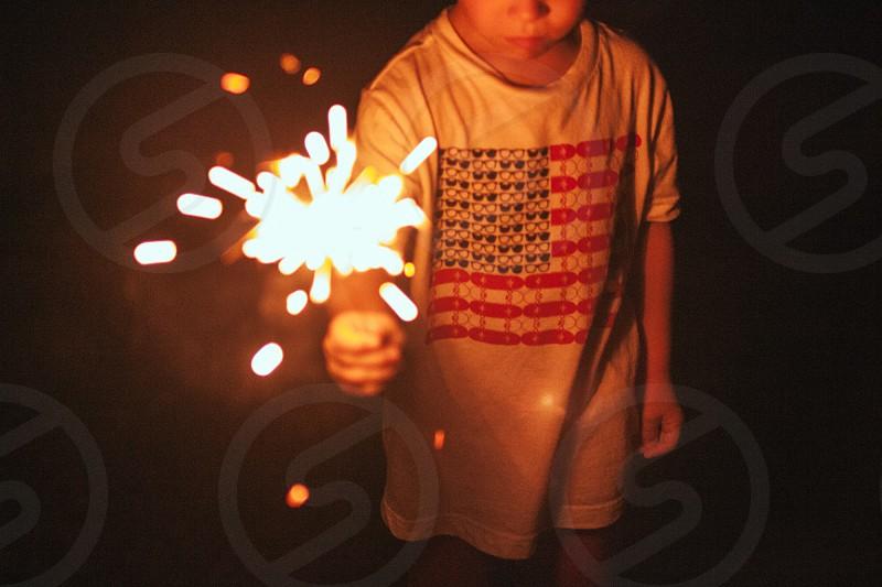 boy in white shirt holding sparkling fireworks photo