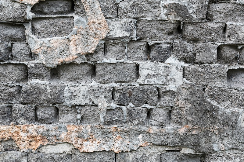 A fragment of old weathered brick wall gray color. photo