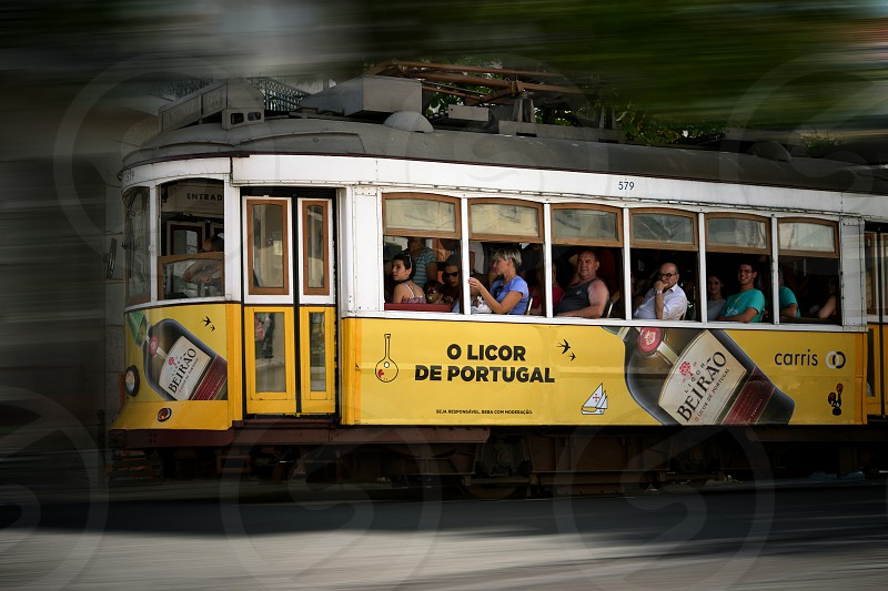 motion blur photo of a white and yellow tram full of passengers photo