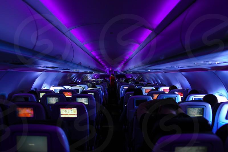 people sitting inside plane with purple lights turned on photo