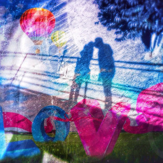 multicolored lovers kissing with balloon photo photo
