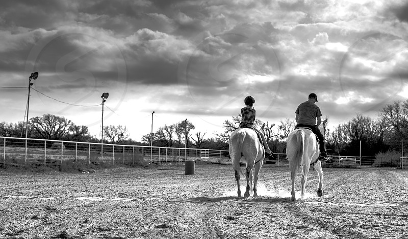 Father and daughter bonding and horseback riding at a ranch. photo