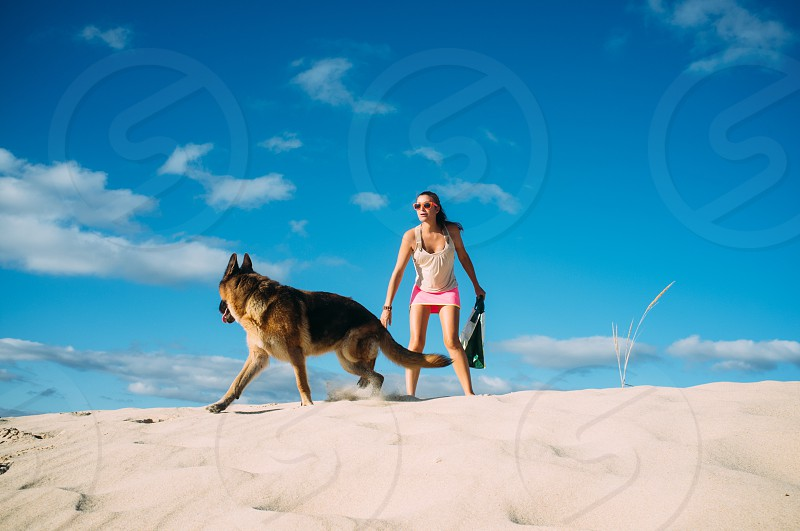Woman Playing with her Pet Dog at the Beach. Pretty Young Woman Playing with her German Shepherd Pet Dog at the Beach on a Tropical Climate. photo