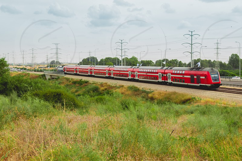 Red israeli passenger train in motion out of the city near Highway 4. photo