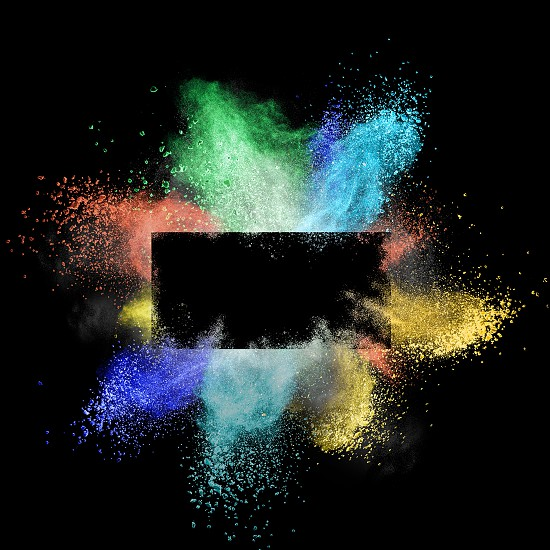 Explosion of a colored powder isolated on a black background around a rectangular frame with a place under the text photo