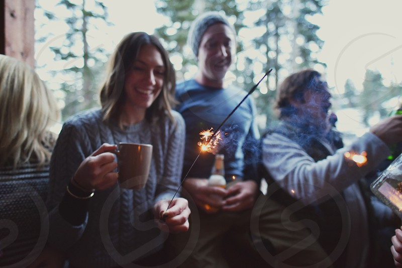 woman sitting with people holding a mug and a fire sparkler photo