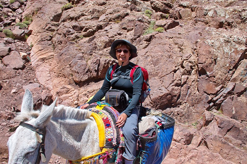 Mature woman riding mule in High Atlas mountains in Morocco photo