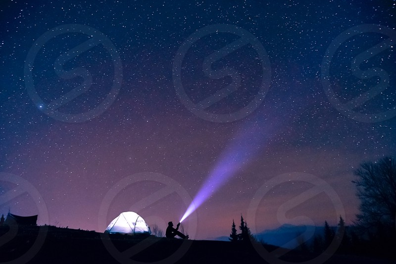 Man tourist with flashlight near his camp tent at night under a sky full of stars. night mountain loneliness photo