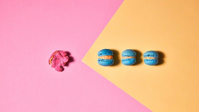 One crushed and three whole macaroons on a yellow pink cardboard background. Flat lay photo