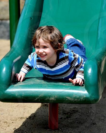 Young boy on a slide enjoying the start of summer. photo