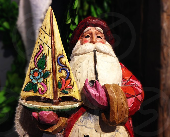 Carved wooden Santa Clause holds a colorful boat photo
