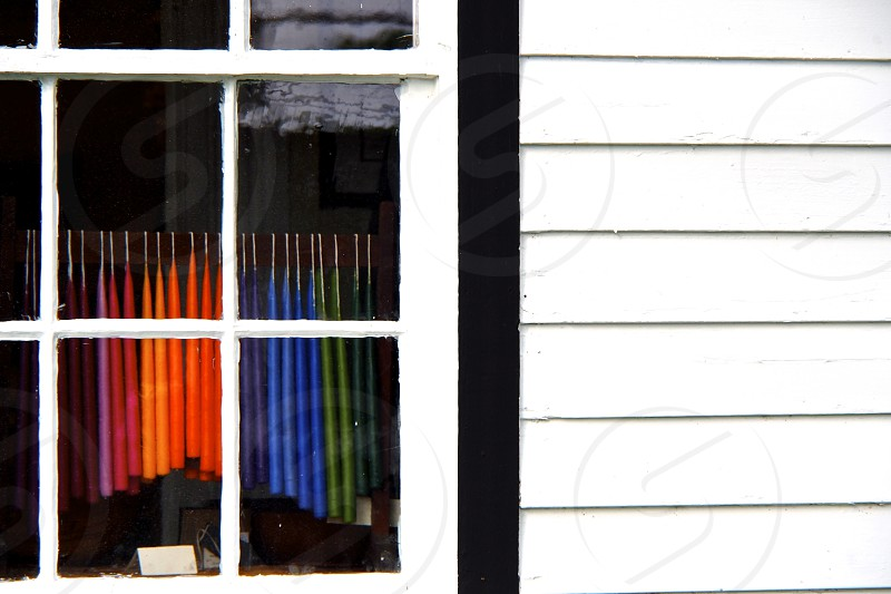Colorful candles in old window. White siding. Colonial bars. Mutton bars. photo