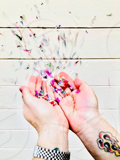 Confetti hand in frame colorful blowing celebrating throwing confetti  photo