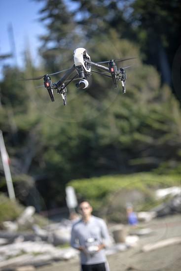 A guy man dude person flies a drone UAV Quadcopter  photo