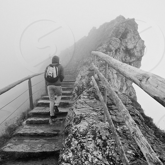 man climbing stairs beside rock face photo