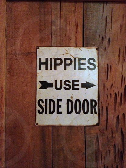 """hippies use side door"" sign on wooden backdrop photo"