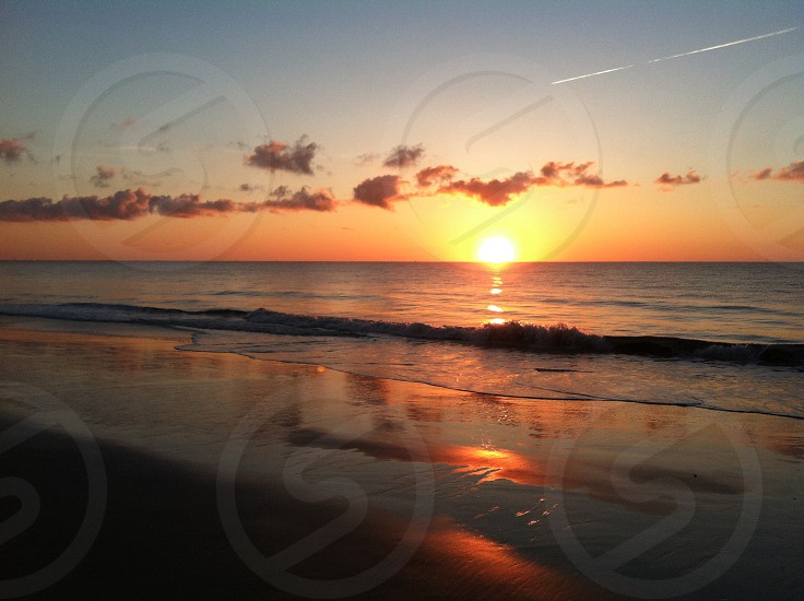 view of sunset by the sea shore photo