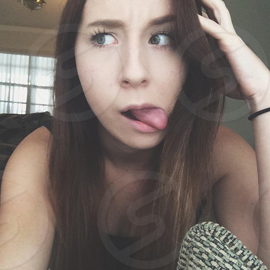 woman in black tank top tongue out photo