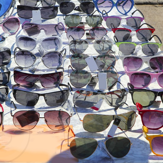 many sunglasses outdoor market shop colorful display photo