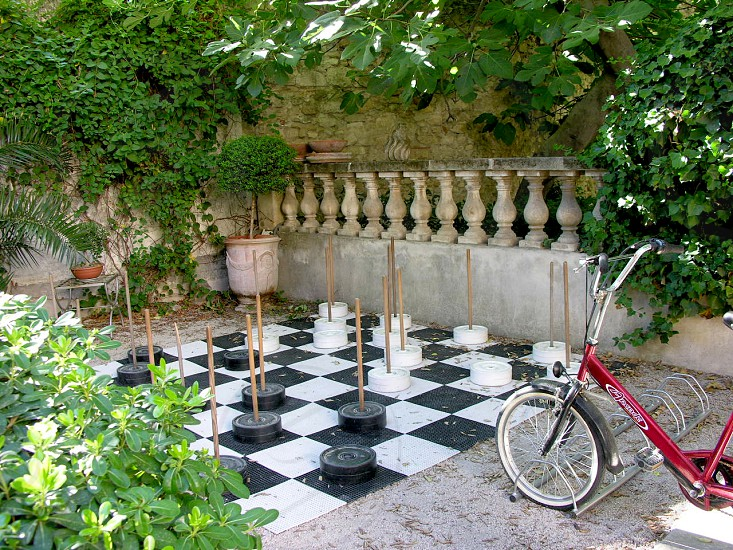 chess large bicycle bike game railing shrubbery plants planters floor giant fun recreation board photo