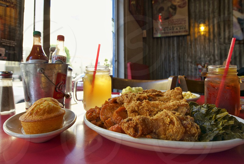 photo of crispy fried chicken beside green vegetable on white ceramic plate and baked cupcake near juice on clear glass mug with red straw near stainless steel coca cola bucket photo