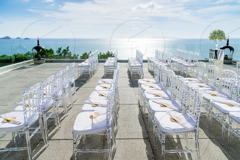 Wedding venue setup on the hill with transparent ghost chairs The sunlight reflection on the sea with panoramic ocean background view Samui Thailand  photo