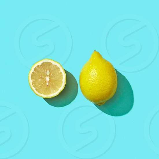 Half and whole a juicy lemon on a blue background with shadow and copy space. Ingredient for drink. Top view photo