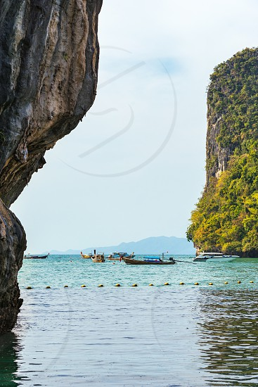 View on sea cliffs and boats in water from Koh Hong Island in Krabi in Thailand photo