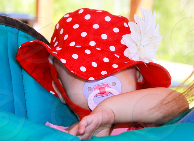 sleeping baby in a red polka dot hat photo