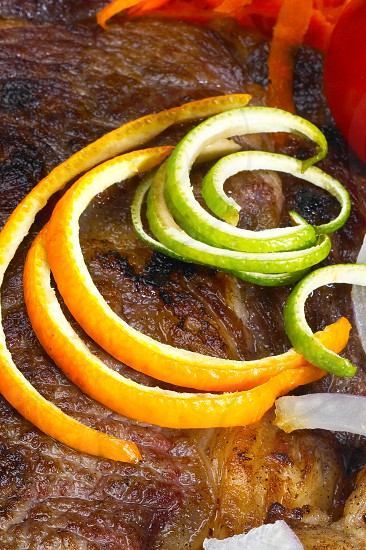 fresh juicy beef ribeye steak grilled with orange and lemon peel on top and vegetables beside photo