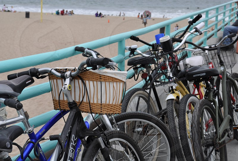 Bikes leaning against the pier fence at the beach.  photo