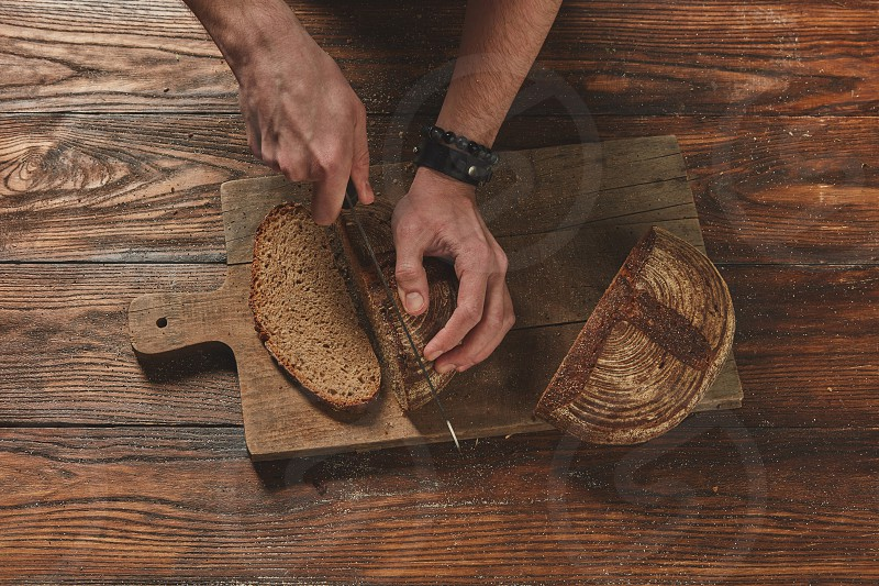 Baker cuts freshly baked organic bread on a wooden brown background flat lay photo